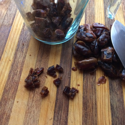 Cup of dates being diced on wooden board with stainless steel knife.